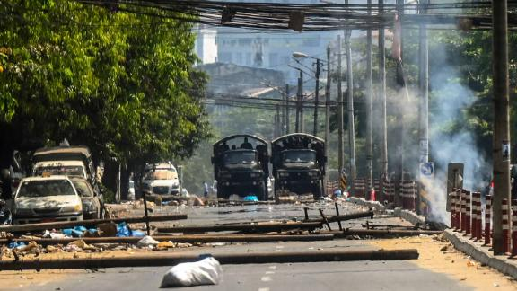 Military trucks are seen near a burning barricade in Yangon that was erected by protesters and then set on fire by soldiers on March 10.