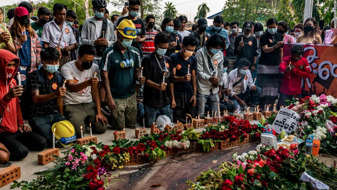 People lay flowers and light candles beside bloodied pavement where protester Chit Min Thu was killed in Yangon.