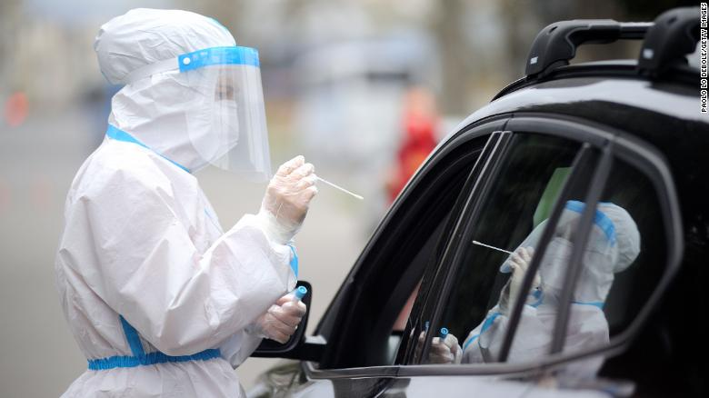 An Italian Red Cross worker takes a swab sample at a drive-through Covid-19 testing station in Florence, Italy on Friday.