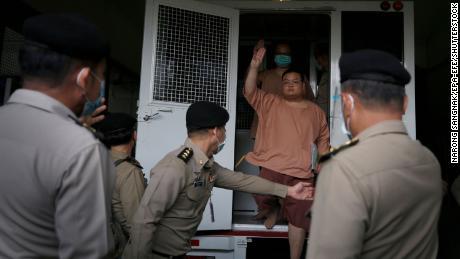 Der thailändische Führer für demokratiefreundliche Aktivisten Parit & # 39;  Pinguin & # 39;  Swarak grüßt mit drei Fingern, als er am 15. März vor dem Strafgericht in Bangkok, Thailand, Anklage erhebt.