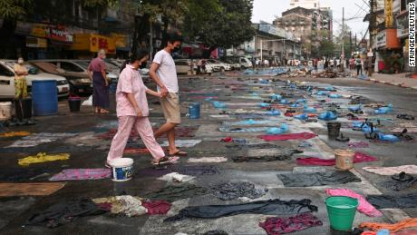 People walk in a street full of water bags to be used against tear gas, during an anti-coup protest at Hledan junction in Yangon, Myanmar, on March 14.