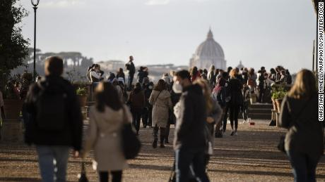 People walk in central Rome, Italy, on March 14, 2021, a day before stricter coronavirus measures came into force.