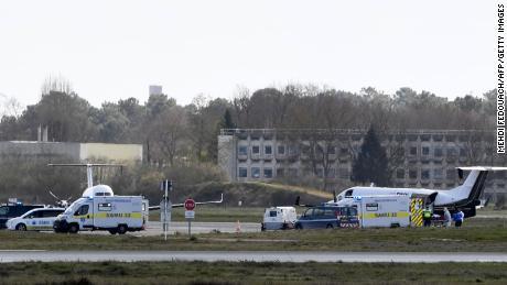 Un patient atteint de la maladie de Covid-19 est transporté dans une ambulance à l'aéroport de Paris dimanche, avant son transfert vers un hôpital d'une autre région.
