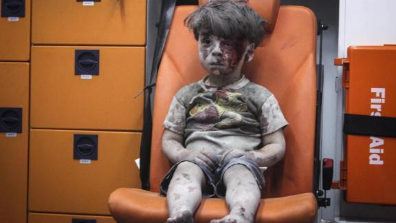 This still image, taken from a video posted by the Aleppo Media Center, shows a young boy in an ambulance after an airstrike in Aleppo, Syria, on August 17, 2016. It took nearly an hour to dig the boy, identified as Omran Daqneesh, out from the rubble, an activist told CNN. The airstrike destroyed his home, where he lived with his parents and two siblings. Director of the Aleppo Media Center Yousef Saddiq said Omran's 10-year-old brother, Ali, died from his injuries.