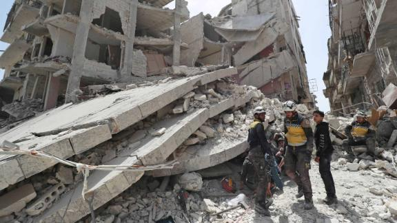 """Members of the Syrian Civil Defence, also known as the """"White Helmets,"""" search the rubble of a collapsed building following an explosion in the town of Jisr al-Shughur on April 24, 2019."""