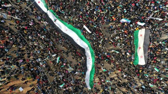 """An aerial picture shows Syrians waving the national flag during a gathering in the rebel-held city of Idlib on March 15, 2021, as they mark <a href=""""https://edition.cnn.com/2021/03/15/middleeast/syria-anniversary-damon-analysis-intl/index.html"""" target=""""_blank"""">10 years</a> since the nationwide anti-government protests that sparked the country's devastating civil war."""