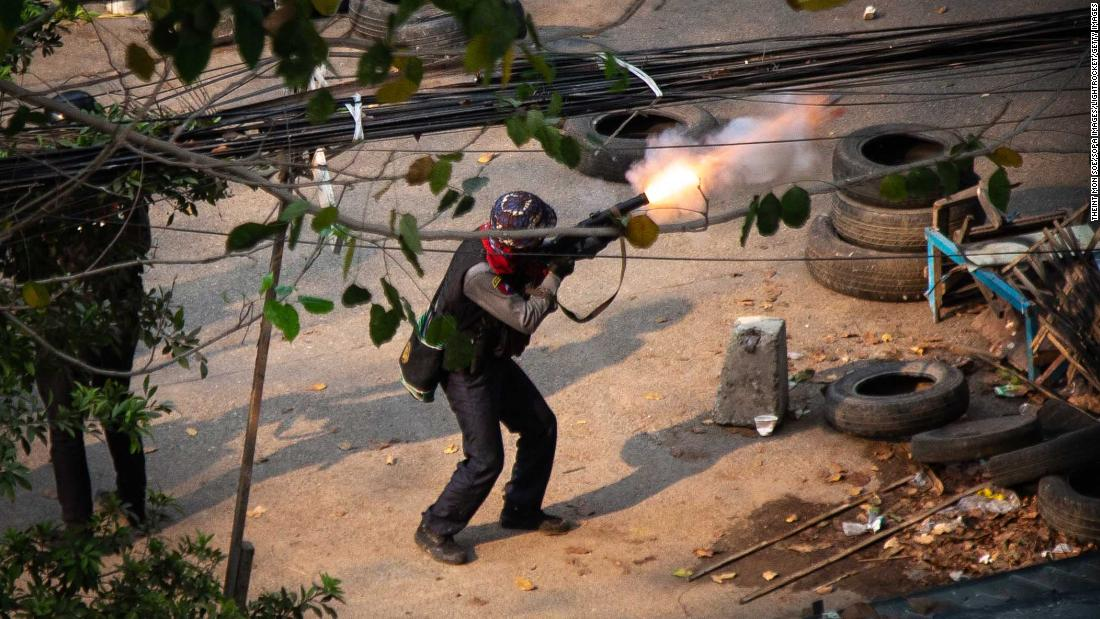 A member of Myanmar's police is seen firing a weapon toward protesters in Yangon on March 13.