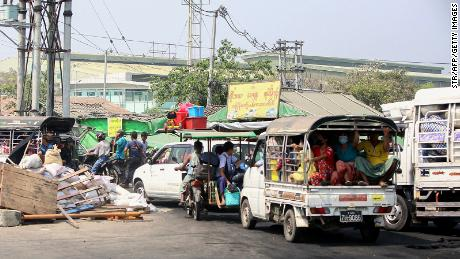 People in cars and trucks flee the Hlaingtharya township in Yangon on March 16, as security forces continue a crackdown on protests in the area.