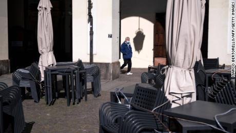 2021 년 3 월 17 일 한 남자가 토리노 비토리오 광장의 닫힌 술집을 지나고있다.