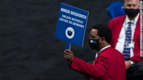 Usher sostiene una pancarta de máscara requerida durante el Torneo de Baloncesto Universitario Masculino en el Big Ten el 11 de marzo en Indianápolis.