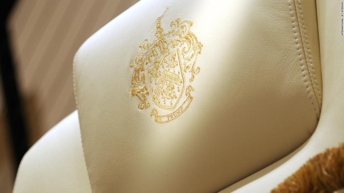 A gold-threaded, embroidered Trump family crest on the headrest of a chair