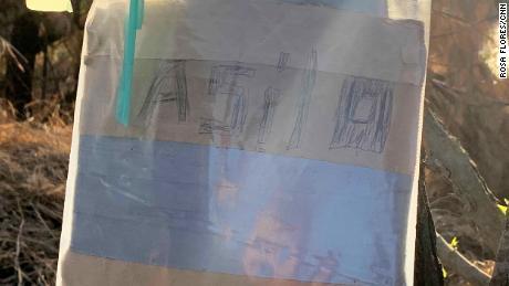 Esta nota garabateada a mano, pegada a un árbol en el sur de Texas, dice & quot;  ASILO & quot;  - Español para & quot;  asilo.  & Quot;