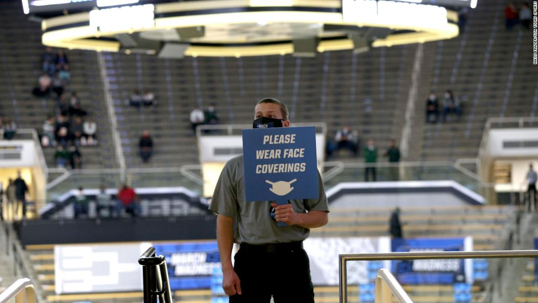 A worker holds a sign encouraging spectators to wear masks before the Michigan State-UCLA game.