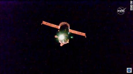 The space station passed through an orbital sunrise during the flight, reflecting red light off the spacecraft.