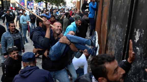 Protesters in Beirut climb a wall installed to prevent them from reaching parliament on March 13.