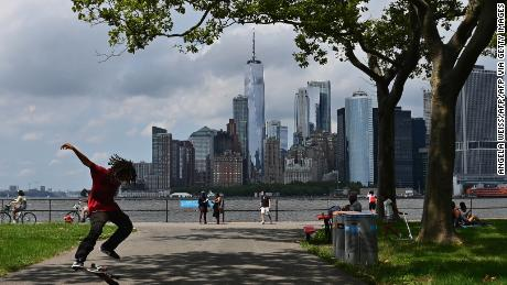 A man skateboards with the Manhattan skyline visible in the distance as people visit Governors Island on July 15, 2020 in New York City.