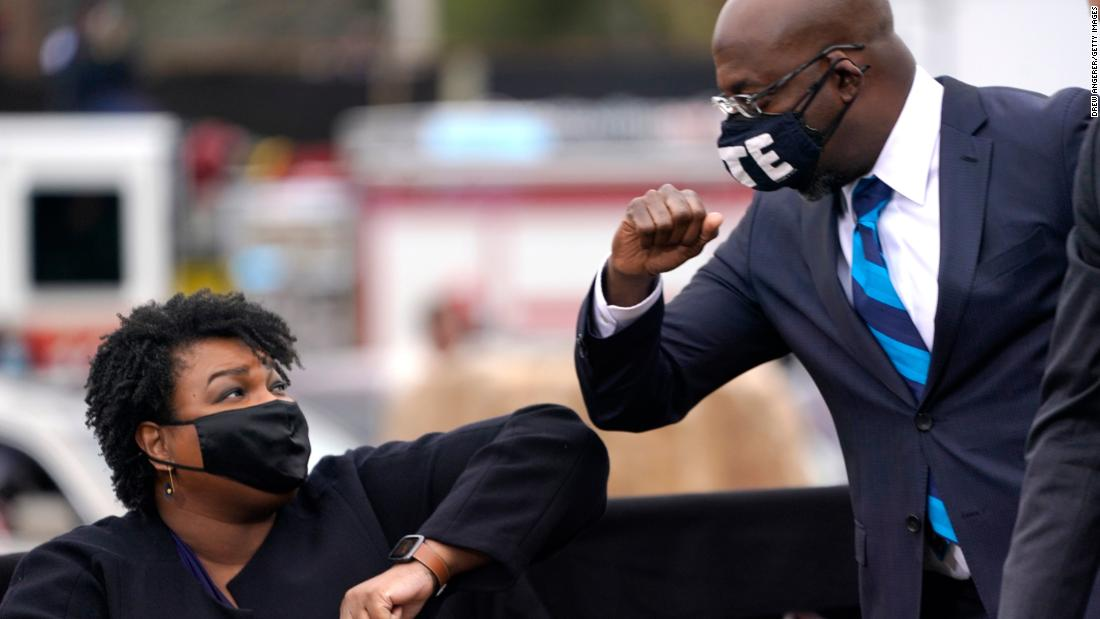 US Senate candidate Raphael Warnock bumps elbows with voting rights leader Stacey Abrams during a campaign rally for Joe Biden on December 15, 2020, in Atlanta.