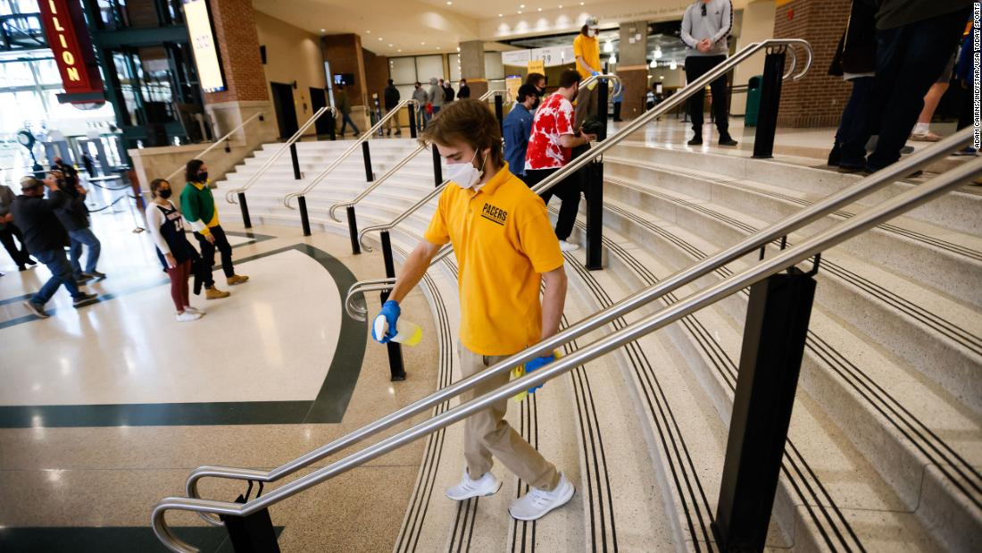 A staff member sprays disinfectant on a handrail at Bankers Life Fieldhouse in Indianapolis.