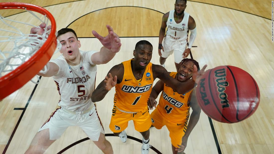 Florida State's Balsa Koprivica, left, hits the boards along with UNC-Greensboro's Isaiah Miller.