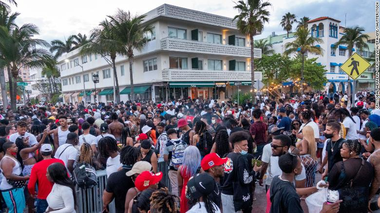 A large crowd of people gathered on a walkway near the beach during spring break in Miami Beach, Florida, on March 20, 2021.