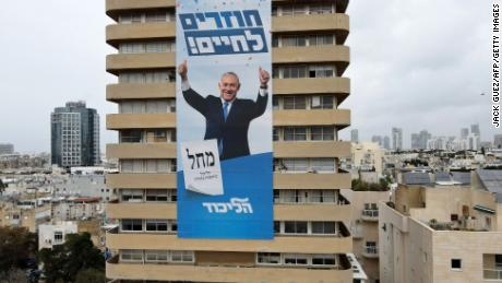 """Netanyahu's campaign slogan """"Come Back to Life"""" hangs on his Likud party headquarters in Tel Aviv."""