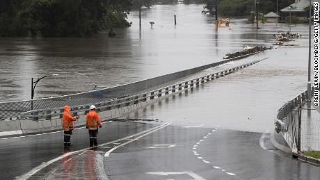 Traffic controllers stand at the Hawkesbury River Bridge, which is inundated by flooding, on March 22nd in Windsor, New South Wales.