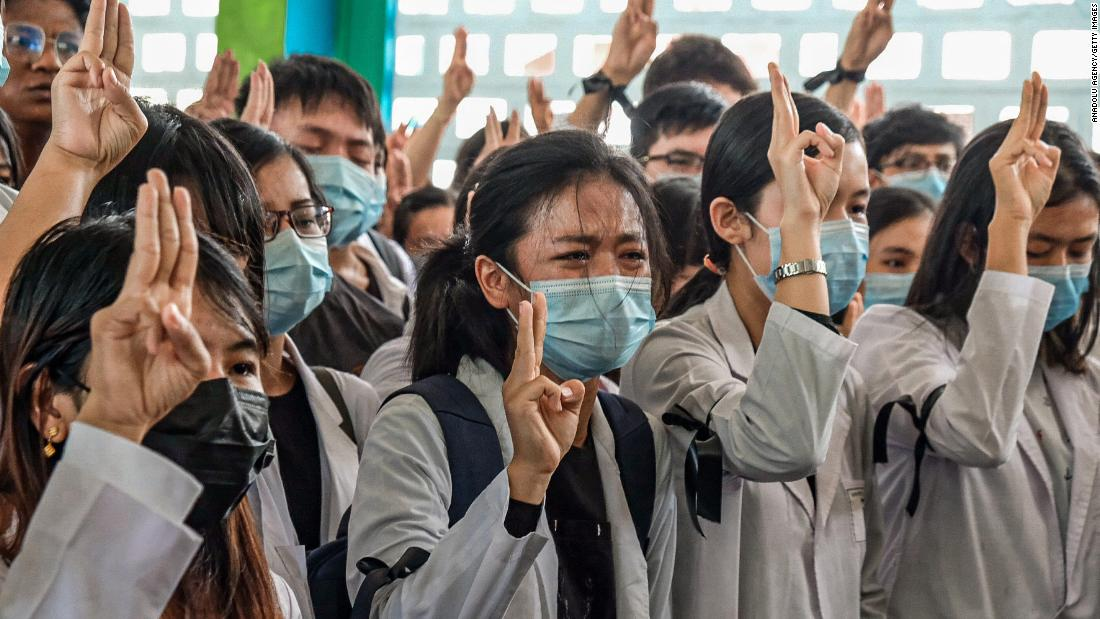 "Medical students hold up the <a href=""https://www.cnn.com/2014/11/20/world/asia/thailand-hunger-games-salute/index.html"" target=""_blank"">three-finger salute</a> at the Yangon funeral of Khant Nyar Hein on March 16. The first-year medical student was fatally shot during the crackdown."
