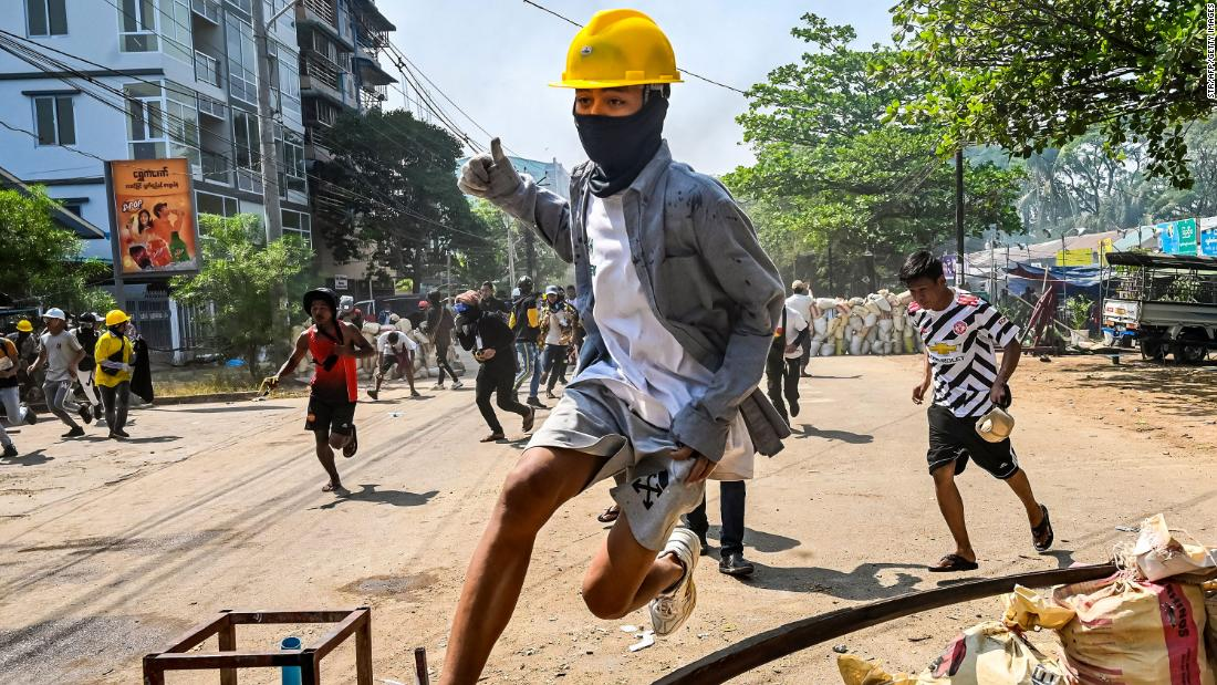 An anti-coup protester jumps over a makeshift barricade in Yangon on Friday, March 19.