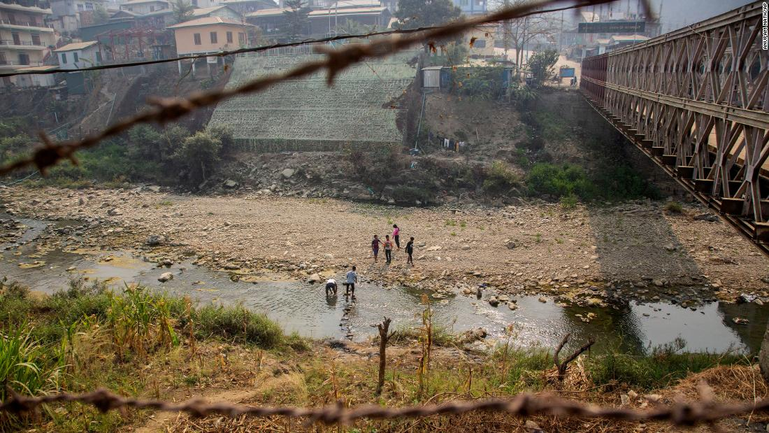 "Unidentified people cross the Tiau River at the India-Myanmar border on March 20. Some people from Myanmar <a href=""https://www.cnn.com/2021/03/11/asia/myanmar-india-mizoram-intl-hnk/index.html"" target=""_blank"">have sought refuge in India</a> since the protests began."