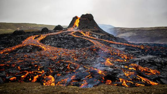 TOPSHOT - Lava flows from the erupting Fagradalsfjall volcano some 40 km west of the Icelandic capital Reykjavik, on March 21, 2021. - Weekend hikers took the opportunity Sunday to inspect the area where a volcano erupted in Iceland on March 19, some 40 kilometres (25 miles) from the capital Reykjavik, the Icelandic Meteorological Office said, as a red cloud lit up the night sky and a no-fly zone was established in the area. (Photo by Jeremie RICHARD / AFP) (Photo by JEREMIE RICHARD/AFP via Getty Images)