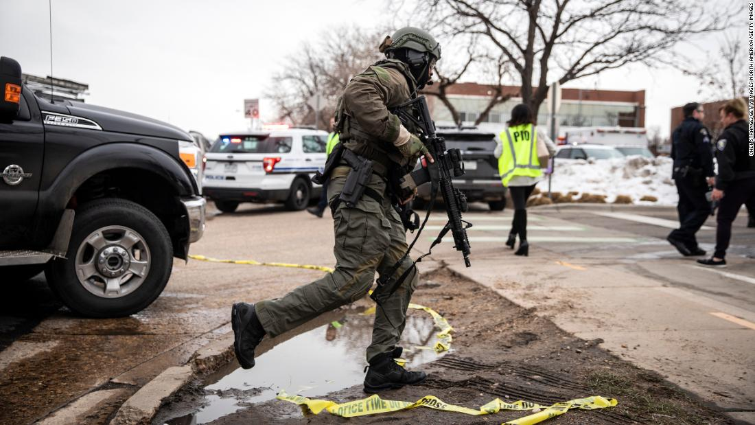 A SWAT team member runs toward the store.