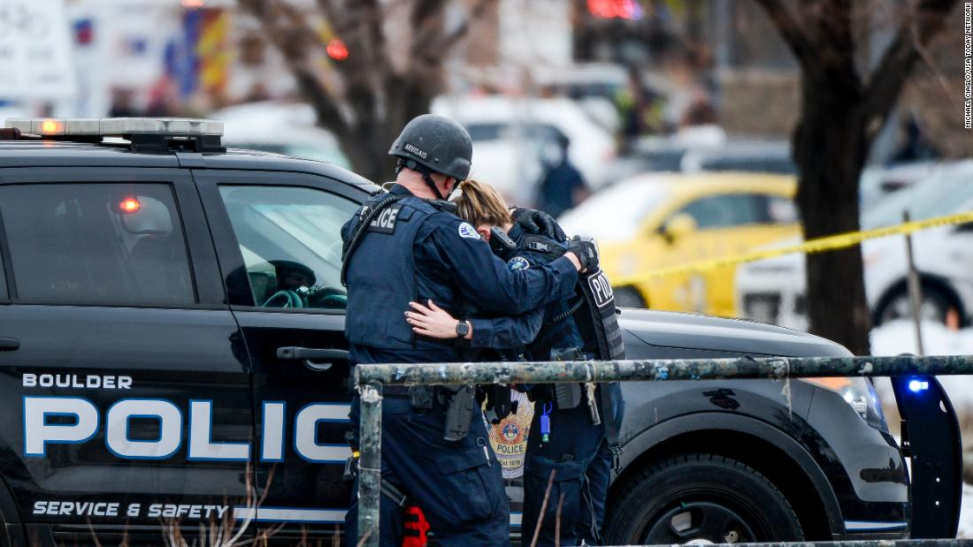 Two police officers embrace each other at the scene.