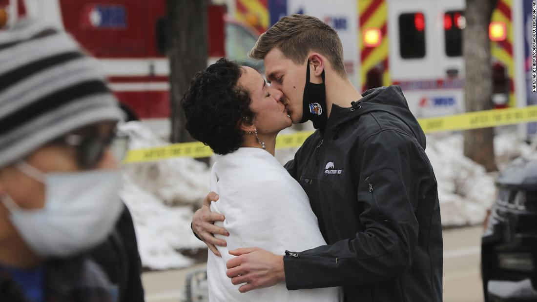 A man and woman kiss near the scene on Monday.
