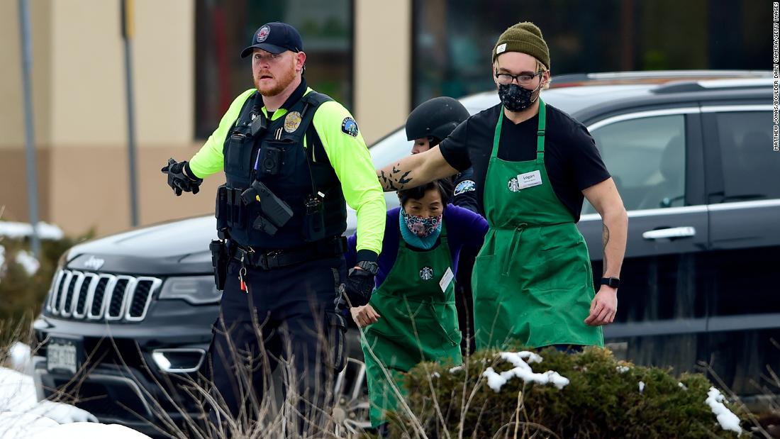 Starbucks employees are helped away from the scene.