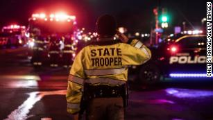 A Colorado State Police officer salutes as a procession carrying the body of a fellow officer leaves King Sooper's grocery store.