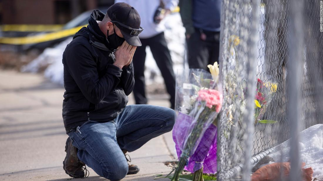 Conrad Wright leaves flowers at the scene on Tuesday, the day after the shooting.