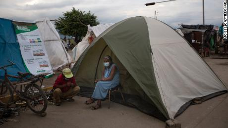 An elderly woman sits outside a tent in Lima, Honduras, where she lives after losing her home in last year's hurricanes Eta and Iota. Devastation from the storms and the economic damage of the Covid-19 pandemic have added to the forces that drive Hondurans to migrate.