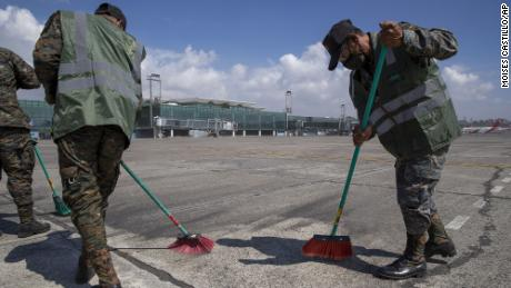 Soldiers sweep volcanic ash from the runway at La Aurora International airport, which was closed following volcanic activity and unfavorable wind conditions at the Pacaya volcano outside of Guatemala City on Tuesday, March 23, 2021.
