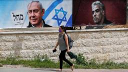 An Israeli woman walks past an electoral poster depicting Israeli Prime Minister Benjamin Netanyahu (L) and one of his challengers Yesh Atid party leader Yair Lapid, in Jerusalem on March 22, 2021. (Photo by AHMAD GHARABLI / AFP) (Photo by AHMAD GHARABLI/AFP via Getty Images)