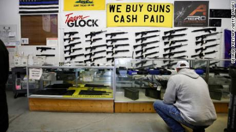 A customer looks at handguns in a case as AR-15 style rifles hang on a wall at Davidson Defense in Orem, Utah on February 4, 2021. - Gun merchants sold more than 2 million firearms in January, a 75% increase over the estimated 1.2 million guns sold in January 2020, according to the National Shooting Sports Federation, a firearms industry trade group.