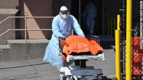 TOPSHOT - Medical staff move bodies from the Wyckoff Heights Medical Center to a refrigerated truck on April 2, 2020 in Brooklyn, New York. - The Federal Emergency Management Agency (FEMA) has asked the US Defense Department for 100,000 body bags as the toll mounts from the novel coronavirus, the Pentagon said on April 2. White House experts have said that US deaths from the disease -- currently at more than 5,100 -- are expected to climb to between 100,000 and 240,000, even with mitigation efforts in force. (Photo by Angela Weiss / AFP) (Photo by ANGELA WEISS/AFP via Getty Images)