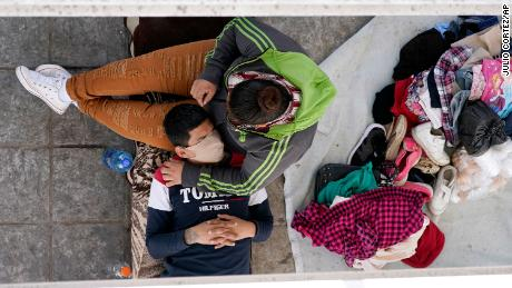Deported migrants rest under a ramp in Reynosa, Mexico, that leads to a bridge at the border.