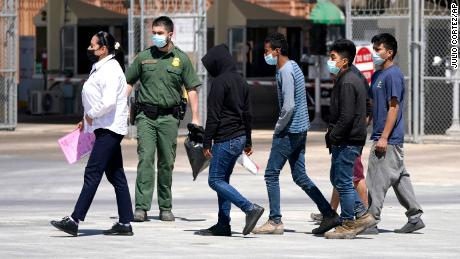Migrants, who were caught trying to sneak into the United States, are led by a U.S. Customs and Border Protection agent, second from left, at the McAllen-Hidalgo International Bridge while being deported to Reynosa, Mexico, Thursday, March 18, 2021, in Hidalgo, Texas. A surge of migrants on the Southwest border has the Biden administration on the defensive. The head of Homeland Security acknowledged the severity of the problem Tuesday but insisted it's under control and said he won't revive a Trump-era practice of immediately expelling teens and children. (AP Photo/Julio Cortez)