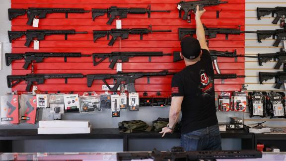 """DELRAY BEACH, FLORIDA - MARCH 24: Brandon Wexler helps a customer look at weapons at WEX Gunworks on March 24, 2021 in Delray Beach, Florida. U.S. President Joe Biden has called on lawmakers to """"immediately pass"""" legislation to help curb gun violence in the county. (Photo by Joe Raedle/Getty Images)"""