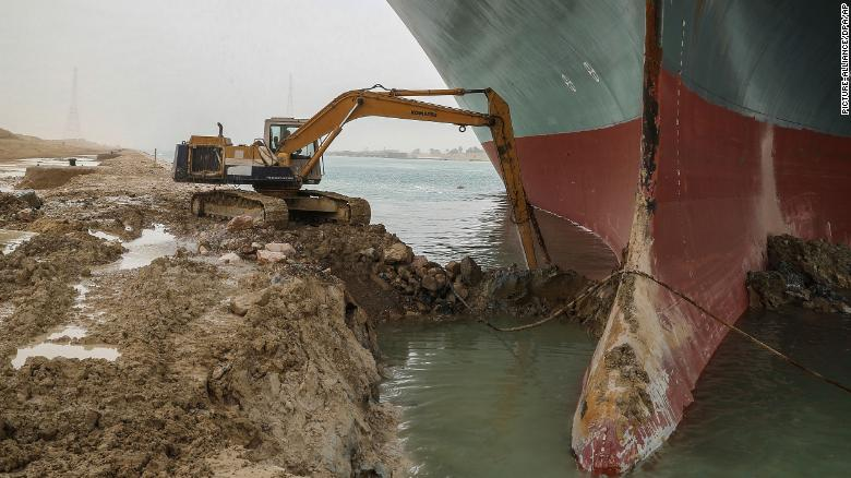 An excavator attempts to free the front end of the container ship.