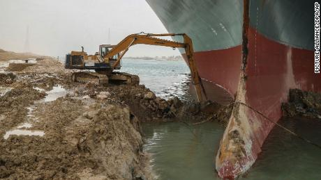 An excavator attempts to free the front end of the Ever Given.