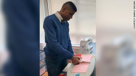 Darius Brown cutting the fabric for a bow tie.