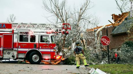 A firefighter surveys damage after a tornado touched down in the Eagle Point community near Birmingham. Alabama.