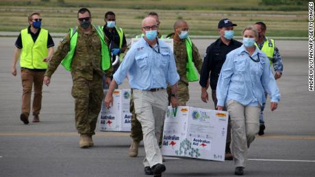 Australian officials carry boxes containing some 8,000 initial doses of the AstraZeneca vaccine at the Port Moresby international airport on March 23.