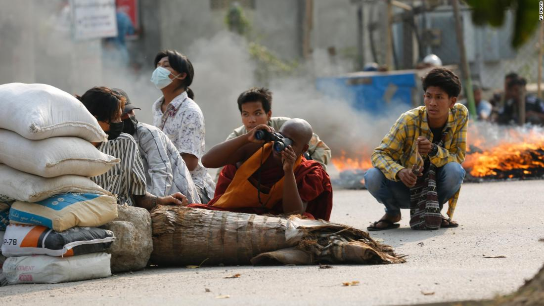 A Buddhist monk uses binoculars as he squats behind a road barricade with others in Mandalay, Myanmar, on March 22.